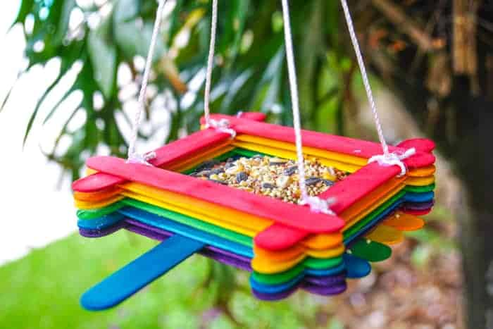 Colourful Popsicle stick birdfeeder hanging from a tree with bird seed in it. Click image to go to craft site.
